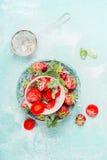 与甜点的平的位置切了在碗的草莓用在浅兰的背景的糖粉 库存照片