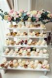 与甜点,糖果,点心,杯形蛋糕,松饼,蛋糕,用花装饰的小饼的结婚宴会立场 免版税图库摄影