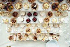 与甜点,糖果,点心,杯形蛋糕,松饼,蛋糕,用花装饰的小饼的结婚宴会立场 图库摄影