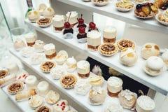与甜点,糖果,点心,杯形蛋糕,松饼,蛋糕,用花装饰的小饼的结婚宴会立场 库存照片