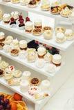 与甜点,糖果,点心,杯形蛋糕,松饼,蛋糕,用花装饰的小饼的结婚宴会立场 免版税库存照片