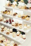 与甜点,糖果,点心,杯形蛋糕,松饼,蛋糕,用花装饰的小饼的结婚宴会立场 免版税库存图片