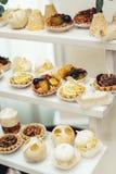与甜点,糖果,点心,杯形蛋糕,松饼,蛋糕,用花装饰的小饼的结婚宴会立场 库存图片