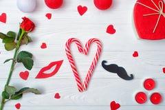 与甜焦糖心脏、一朵红色玫瑰、礼物和蜡烛的情人节背景 假日装饰 库存照片