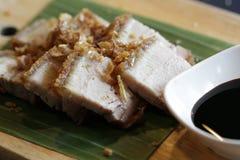 与甜黑调味汁食谱顶部的特写镜头中国酥脆猪肉与在香蕉叶子和棕色木板材的油煎的大蒜服务 库存图片