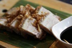 与甜黑调味汁食谱顶部的特写镜头中国酥脆猪肉与在香蕉叶子和棕色木板材的油煎的大蒜服务 免版税库存照片
