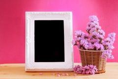 与甜statice花的白色葡萄酒照片框架在篮子wi 图库摄影
