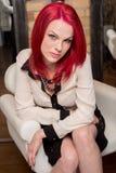 与生动的红色头发的模型在椅子 免版税库存图片