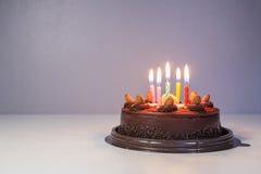 与生日光蜡烛的巧克力蛋糕 库存照片