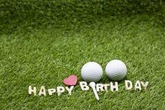 与生日快乐标志的高尔夫球在绿草 免版税库存图片