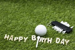 与生日快乐标志的高尔夫球在绿草 库存照片