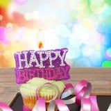 与生日快乐蜡烛的一块生日杯形蛋糕 库存照片