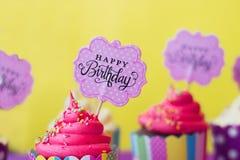 与生日快乐贺卡的鲜美草莓杯形蛋糕在y 免版税库存照片