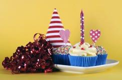 与生日蜡烛的明亮和爽快红色蓝色和黄色题材杯形蛋糕 库存图片