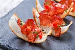 与生涩的熏火腿的开胃菜bruschetta在石板岩背景关闭的稀薄地切的ciabatta面包  库存图片