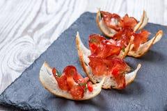与生涩的熏火腿的开胃菜bruschetta在石板岩背景关闭的稀薄地切的ciabatta面包  免版税库存照片