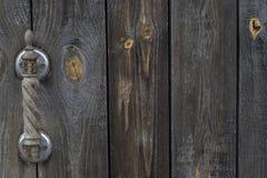 与生锈的木被雕刻的瘤的老破旧的木门 免版税图库摄影