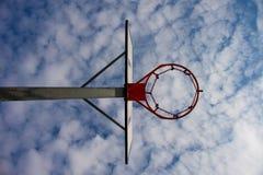 与生锈的箍的老忽视篮球档板在街道法院上 在bckground的蓝色多云天空 减速火箭的过滤器 免版税库存图片