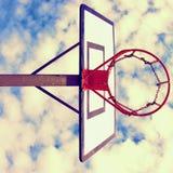 与生锈的箍的老忽视篮球档板在街道法院上 在bckground的蓝色多云天空 减速火箭的过滤器 库存照片