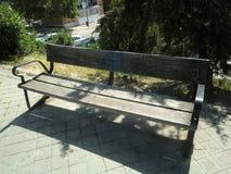 与生锈的螺丝的老长木凳在一个春日 免版税库存图片