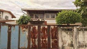 与生锈的表面的前门和后边是附近房子 免版税库存照片