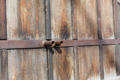 与生锈的金属把柄,背景的自然木门 免版税库存照片