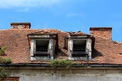 与生锈的金属花持有人的两个被毁坏的屋顶窗口在与残破和缺掉瓦的被放弃的老大厦 库存照片