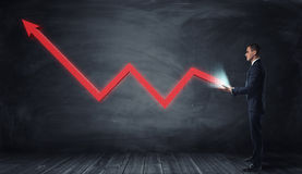 与生长从商人手的一个向上的箭头的巨大的红线图表 图库摄影