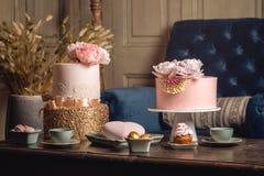 与用乳香树脂和玫瑰色金子装饰的一个美丽的桃红色蛋糕的豪华婚礼桌在古色古香的经典内部 免版税库存图片