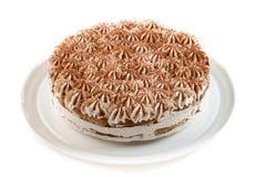 与用在被隔绝的白色背景的巧克力片装饰的打好的奶油的蛋糕 免版税图库摄影