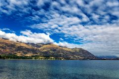 与用山盖的美丽的小山的瓦纳卡湖视图 免版税库存图片