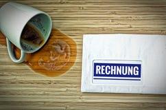与用德语Rechnung的信件在英国票据和从惊吓的一个被倾销的咖啡杯 库存图片