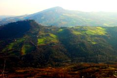 与用森林和草甸盖的巨型的小山的风景 免版税图库摄影
