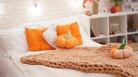 与用粗糙的毛线一条被编织的毯子盖的轻的床单的床  在床上的卧室是南瓜纺织品 免版税库存图片