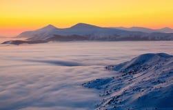 与用织地不很细雪和山的风景盖的一座惊人的日落、有趣的大雾在一个冬日 免版税库存图片