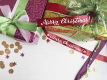 与用缎圣诞快乐丝带和书法装饰的当前箱子的平的位置构成  库存照片