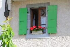 与用花装饰的绿色快门的木窗口在吕特里,瑞士小村庄  库存照片