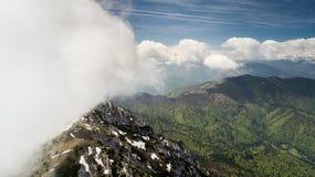 与用雪和云彩报道的山峰的春天风景 免版税库存照片