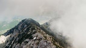 与用雪和云彩报道的山峰的春天风景 免版税库存图片