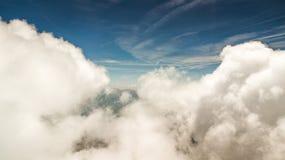 与用雪和云彩报道的山峰的春天风景 免版税图库摄影