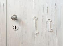 与用2把钥匙装饰的匙孔的老破裂的灰色门 免版税库存照片