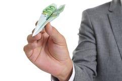 与用100欧元钞票做的纸飞机的商人 免版税库存图片