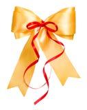 与由丝绸做的红色丝带的金黄弓 图库摄影
