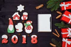 与由姜饼曲奇饼做的杉树,有笔的,杉树空白的白色笔记本的圣诞节背景分支和红色礼物 图库摄影