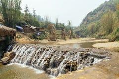 与由竹子和树做的精心制作的水轮的瀑布在背景中在夏天在猫猫村庄Sa Pa的,越南 免版税库存图片