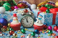 与由糖果店乳香树脂做的色的装饰雪人的圣诞节杯形蛋糕 图库摄影