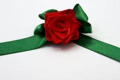 与由缎丝带用手做的绿色瓣的红色玫瑰 免版税库存图片