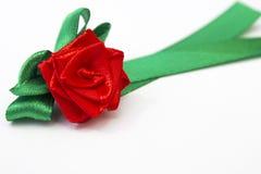 与由缎丝带用手做的绿色瓣的红色玫瑰 库存照片