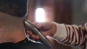 与电剃刀的男性理发 关闭头发整理者发型 剪有头发的专业美发师头发 影视素材