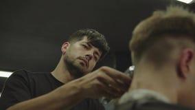 与电剃刀的男性理发 关闭头发整理者发型 理发师做客户的理发在理发店 股票录像